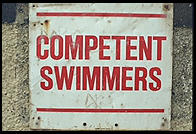 Sign advising that only competent swimmers enter the rough waters of the Irish Sea on a rocky beach north of Dublin, Ireland.