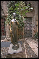 Statue of Shakespeare's Juliet, Verona.  Note the shine on her right breast from the rubbing of tourists' hands.  Note further the doorway behind the statue where lovers leave notes.