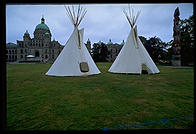 Teepees and a totem pole on the front lawn of the enormous stone parliament building, Victoria, British Columbia.