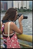 Woman photographing dragon boat racing.  Sha Tin, Hong Kong